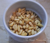 Measure out pine nuts and roast either in the oven or in a pan on the stove top
